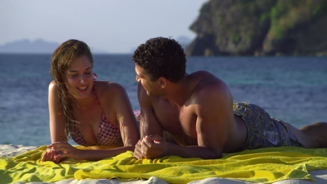 ms happy young couple relaxing on tropical beach, krabi, thailand - 水泳パンツ点の映像素材/bロール