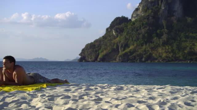 ws pan happy young couple relaxing on tropical beach, krabi, thailand - 水泳パンツ点の映像素材/bロール