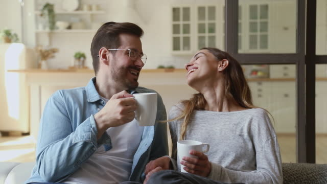 Happy young couple relaxing talking laughing drinking coffee tea