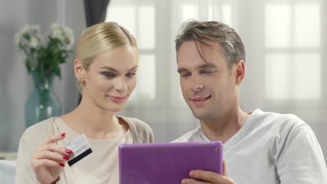 幸せな若いカップルショッピングオンラインにて。を使用して、クレジットカード、ipad のリビングルーム - 金銭に関係ある物点の映像素材/bロール