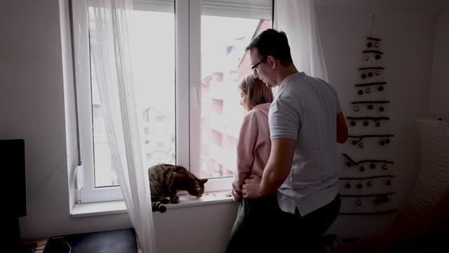 vídeos y material grabado en eventos de stock de feliz pareja joven de pie junto a la ventana en casa - refugiarse en un lugar concepto
