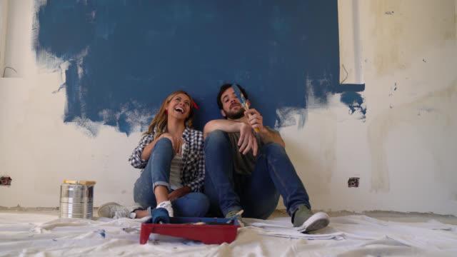 vídeos y material grabado en eventos de stock de feliz joven pareja tomando un descanso de su mejora de casa apoyado en la pared riendo - solar de construcción