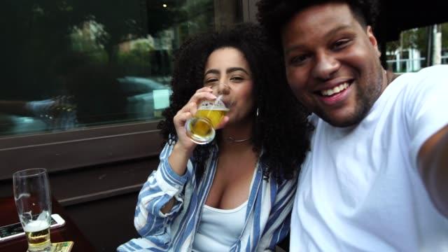 vídeos de stock, filmes e b-roll de casal jovem feliz tendo uma selfie num bar - cerveja