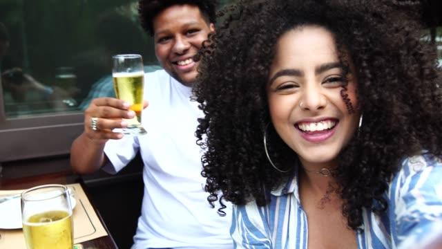 vídeos y material grabado en eventos de stock de feliz pareja joven teniendo un selfie en un bar - 25 29 años
