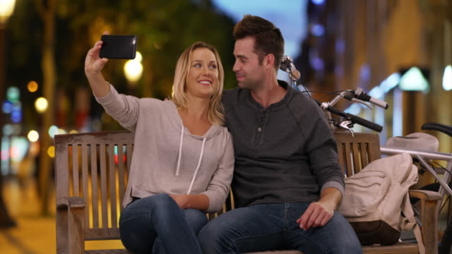 happy young couple taking a selfie on the champs-elysees at night - 自分撮り点の映像素材/bロール