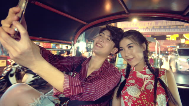 happy young couple taking selfie portrait on tuk tuk taxi in bangkok city. - portable information device stock videos & royalty-free footage
