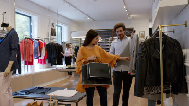 happy young couple talking and grabbing a sweater from a clothing rack at a clothing boutique - mid adult men stock videos & royalty-free footage