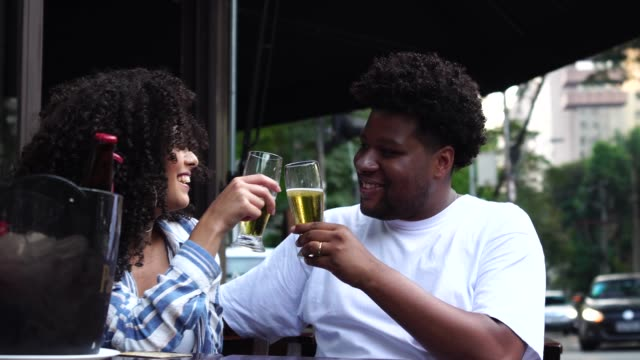 Happy young couple toasting with beer in a bar