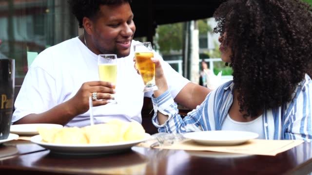 glückliches junges paar toasten mit bier in einer bar - freitag stock-videos und b-roll-filmmaterial