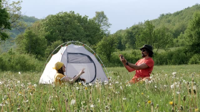 happy young couple tourists camping in the nature and taking selfies. enjoyment outdoors on a sunny day. - dandelion stock videos & royalty-free footage