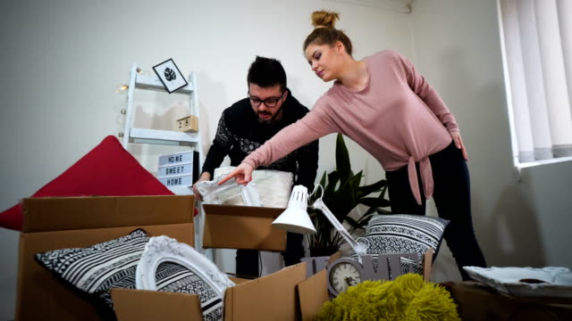 happy young couple unpacking or packing boxes and moving into a new home - relocation stock videos & royalty-free footage