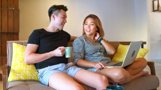 vidéos et rushes de heureux jeune couple à l'aide d'ordinateur portable à la maison - assis en tailleur