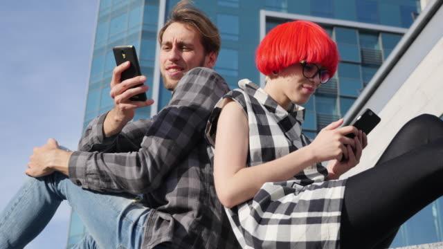 glückliches junges paar mit smartphones in der stadt - 20 29 years stock-videos und b-roll-filmmaterial