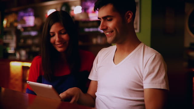 happy young couple using touchpad in a cafe - electronic organizer stock videos and b-roll footage