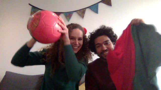 vídeos de stock, filmes e b-roll de happy young couple wave and cheer for their team over a video call - incentivo