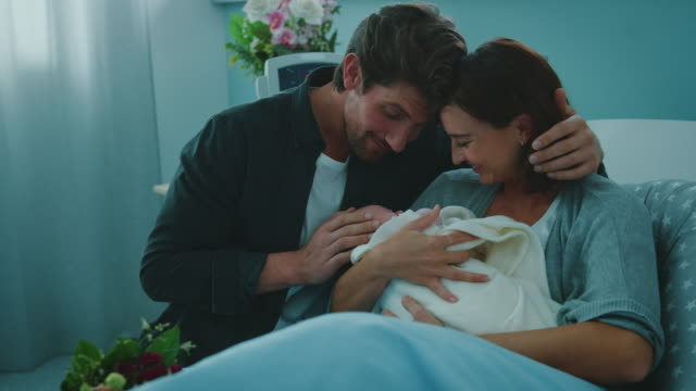 Happy young couple with newborn baby in hospital