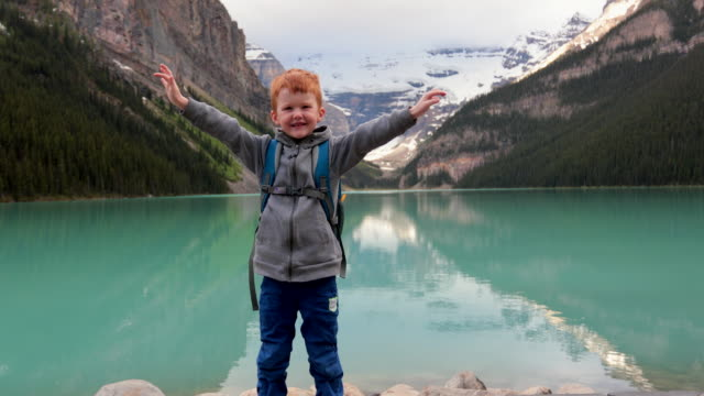 happy young cute redhead boy with arms raised at lake louise in summer - sustainable tourism stock videos & royalty-free footage