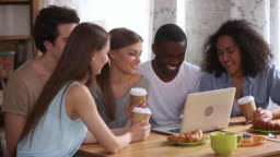 Happy young diverse friends having fun watching comedy on laptop