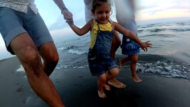happy young family having fun on beach at sunset - beach holiday stock videos & royalty-free footage