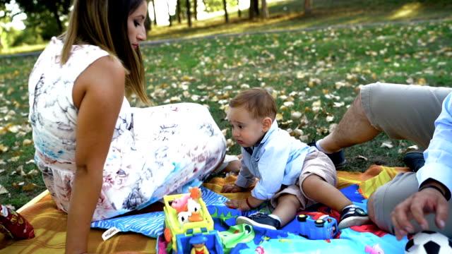 vidéos et rushes de jeune famille heureuse ayant le pique-nique dans le stationnement - picnic