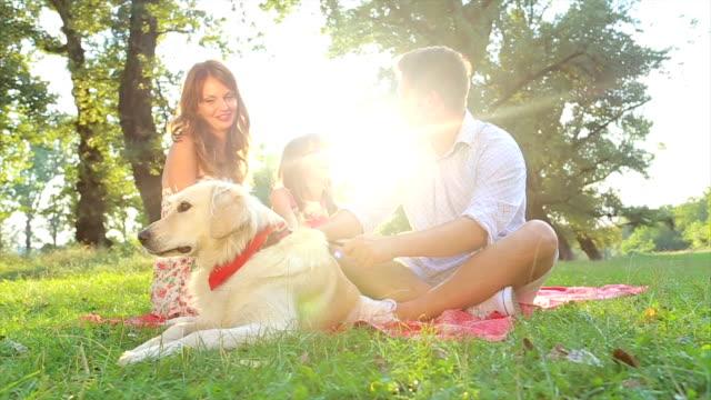 Felice giovane famiglia in un giorno d'estate con cane