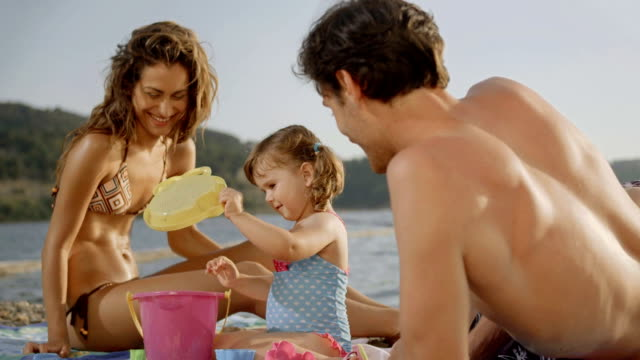 hd: happy young family on the beach - beach holiday stock videos & royalty-free footage