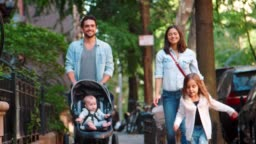 Happy young family walking in a Brooklyn street