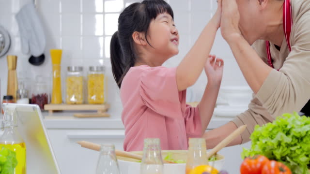 happy young family with dad and young girl cooking in the kitchen preparing a meal together.modern families - single father stock videos & royalty-free footage