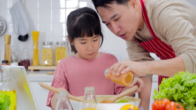 happy young family with dad and young girl cooking in the kitchen preparing a meal together.modern families - happy meal stock videos & royalty-free footage
