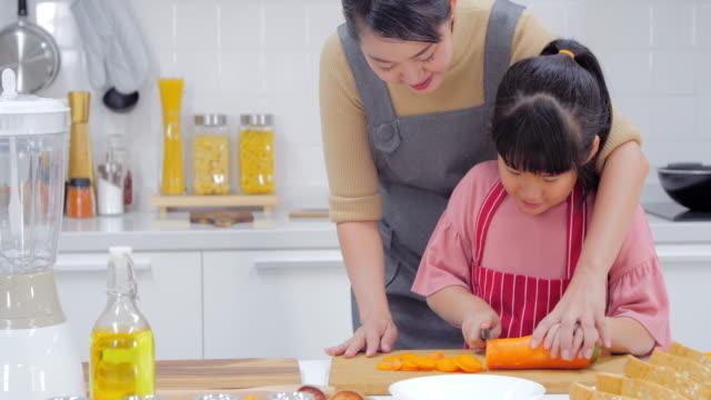 vídeos de stock, filmes e b-roll de família de jovem feliz com a mãe, pai e jovem garota cozinhando na cozinha preparando uma refeição juntos - happy meal