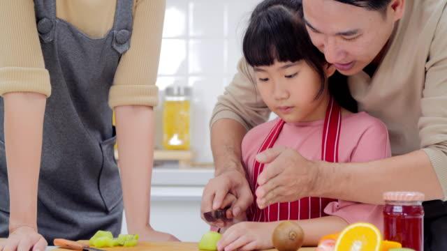 vídeos de stock, filmes e b-roll de família feliz jovem com a mãe, pai e jovem garota cozinhando na cozinha preparando uma refeição juntos. tailandês famílias em casa - happy meal