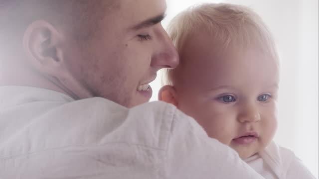 vidéos et rushes de heureux jeune père portant son bébé - personnes belles