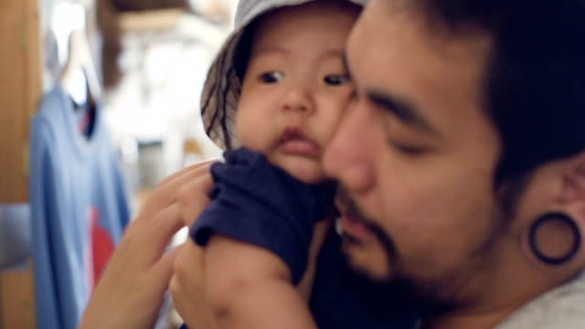 happy young father carrying his baby - leanincollection stock videos & royalty-free footage