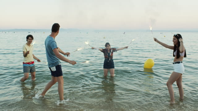 happy young friends dancing in the sea with sparklers - image stock videos & royalty-free footage