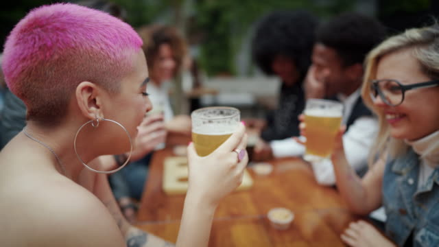 happy young friends enjoying beer and good laugh together at outdoor pub - hipster culture stock videos & royalty-free footage