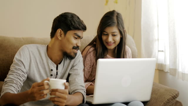 happy young friends using laptop - indian ethnicity stock videos & royalty-free footage