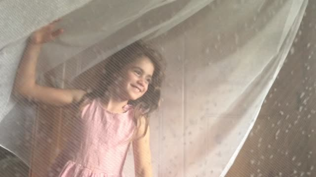 Happy Young Girl Dancing and Playing Inside a Curtain