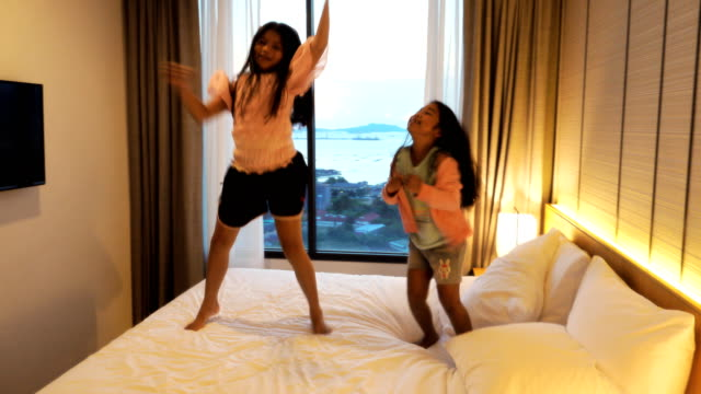 happy young girl dancing on the bed in her bedroom - bouncing stock videos & royalty-free footage