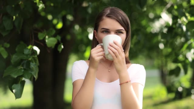 happy young girl drinks tea - portrait with a cup - hd video - video portrait stock videos & royalty-free footage