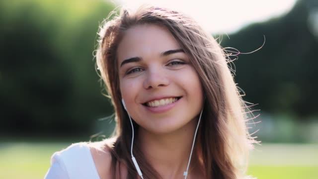 vidéos et rushes de heureuse jeune fille dans la vidéo hd de parc - écoute de la musique- - vidéo portrait