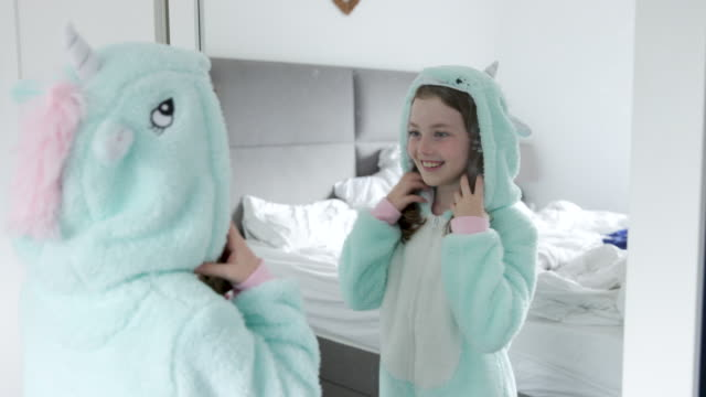 vidéos et rushes de happy young girl looking at her reflection in the mirror - pyjama