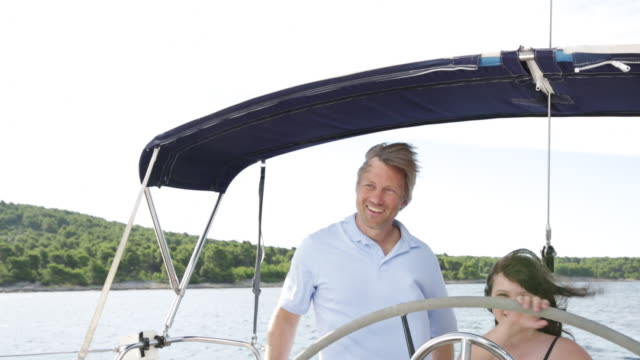 cu happy young girl steering yacht as dad gives guidance beside her. - tutina video stock e b–roll