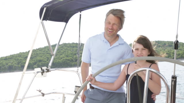 cu happy young girl steering yacht with dad's support. - tutina video stock e b–roll