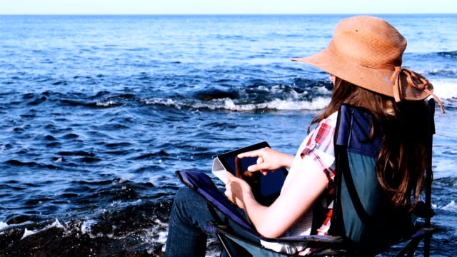 A happy young girl with a tablet on the rocky beach at sunrise.