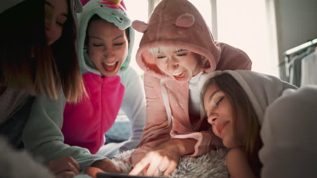 happy young girlfriends at a sleepover having fun while checking social media on the smart phone. - slumber party stock videos & royalty-free footage