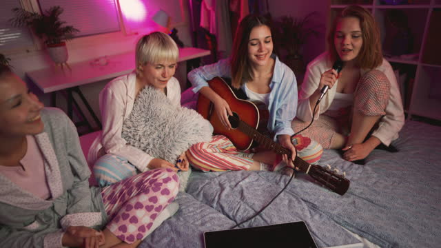 happy young girlfriends singing karaoke at a slumber party - slumber party stock videos & royalty-free footage