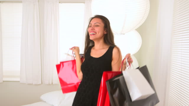 happy young hispanic woman with shopping bags spinning around - straight hair stock videos & royalty-free footage