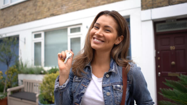 happy young home owner holding keys to her house and looking at camera smiling - for sale frase inglese video stock e b–roll