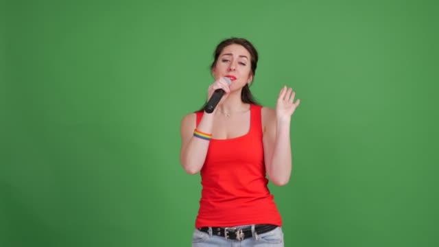 幸せな若いレズビアン ダンスは、緑色の背景で歌う - カットアウト点の映像素材/bロール