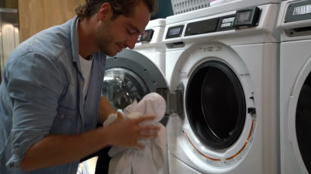 happy young man at a laundromat loading washing machine - launderette stock videos & royalty-free footage